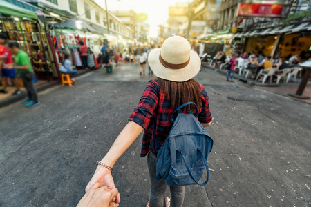 Foto de Back side of Young Asian traveling women leading by holding her boyfriend hand in Khaosan Road walking street in evening at Bangkok, Thailand, traveleling together and tourist with follow me concept - Imagen libre de derechos
