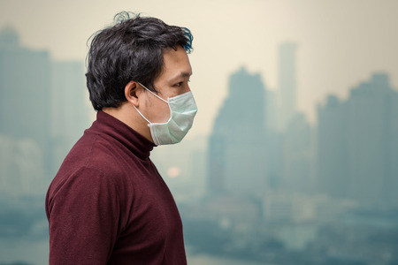 Foto de Asian man wearing the face mask against air pollution at the balcony of High Apartment which can see pollution and heavy fog over the bangkok cityscape background, healthcare concept - Imagen libre de derechos