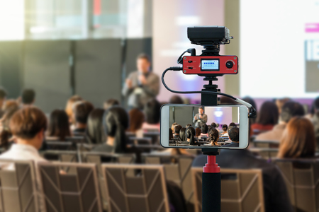 Foto de Closeup smart mobile phone taking Live over Speakers on the stage with Rear view of Audience in the conference hall or seminar meeting, technology live streaming and broadcast concept - Imagen libre de derechos