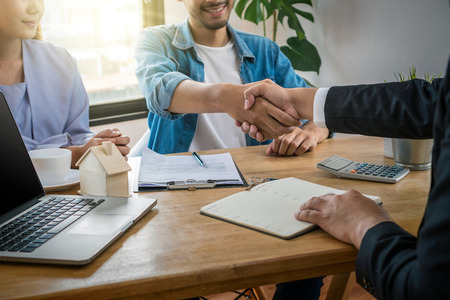 Foto de Closeup Hand shake between sale representative and house owner when sign contact of house purchase or rental on the working space table in new house,Moving and House Hunting concept, - Imagen libre de derechos