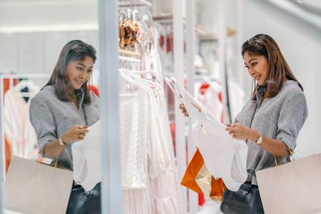 Photo for Asian woman looking and choosing the underwear in store shop with happy action at department center - Royalty Free Image
