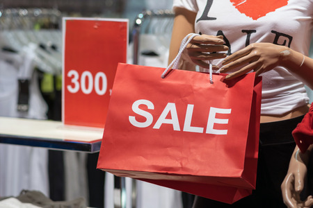 Part of female mannequin dressed in casual clothes holding the Sales paper shopping bag in the shopping department store for shopping, business fashion and advertisement concept