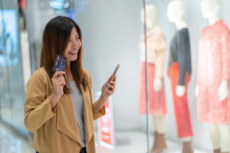 Asian woman using credit card with mobile phone for online shopping in department store over the clothes shop store background, technology money wallet and online payment concept, credit card mockup