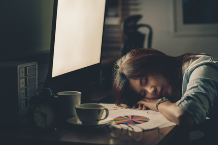 Foto per Portrait of Asian Businesswoman hard working and sleeping on the table with front of computer desktop in workplace at late with serious action, Work hard and too late concept - Immagine Royalty Free