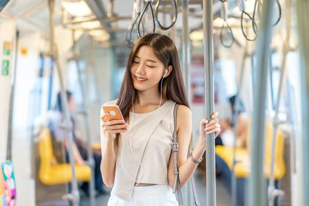 Photo pour Young Asian woman passenger listening music via smart mobile phone in subway train when traveling in big city,japanese,chinese,Korean lifestyle and daily life, commuter and transportation concept - image libre de droit