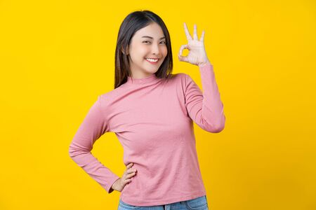 Photo for Asian smiling young woman gesturing ok sign for approval or agreement on isolated yellow color background, wearing winter cozy sweater indoors studio,happiness and optimistic decision copy space - Royalty Free Image