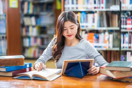 Photo pour Asian young Student in casual suit doing homework and using technology teblet in library of university or colleage with various book and stationary over the book shelf background, Back to school - image libre de droit