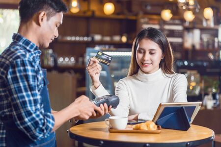 Photo pour Asian customer woman paying with credit card via contactless technology to Asian Small Coffee shop owner at the female table in cafe, Small business owner and startup in coffee shop concept - image libre de droit