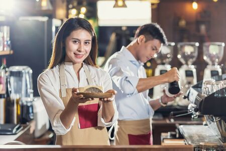Asian Barista serving bakery cake, preparing cup of coffee, espresso with latte or cappuccino for customer order in coffee shop,Small business owner and startup in coffee shop and restaurant concept