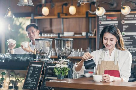 Asian Barista preparing cup of coffee, espresso with latte or cappuccino for customer order in coffee shop,bartender pouring milk,Small business owner and startup in coffee shop and restaurant concept