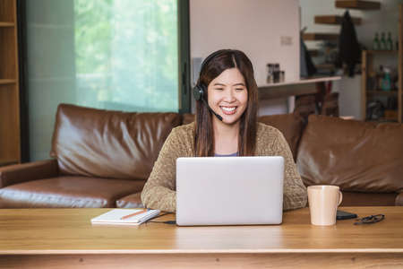 Photo pour Asian business woman using technology laptop and headphone for working from home in indoor house by video conference call, startups and business owner, social distance and self responsibility - image libre de droit