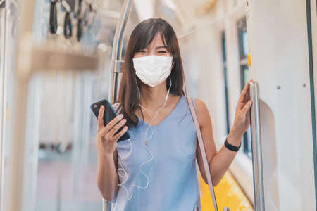 Photo pour Young Asian woman passenger wearing surgical mask and listening music via smart mobile phone in subway train when traveling in big city at Covid19 outbreak, Infection and Pandemic concept - image libre de droit