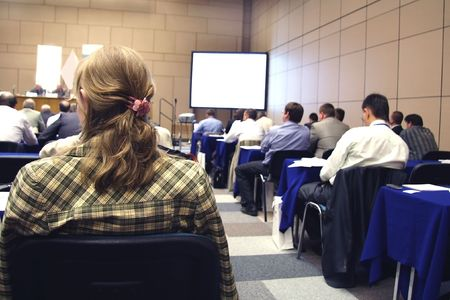 Meeting in a conference hall. Focus is under the hair of the lady in the left part of the image