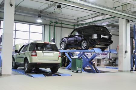 Photo pour Cars on the elevator in a repair garage - image libre de droit