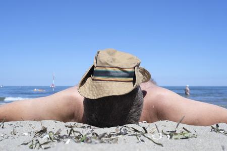 man sunbathes on the beach with a cap on the head