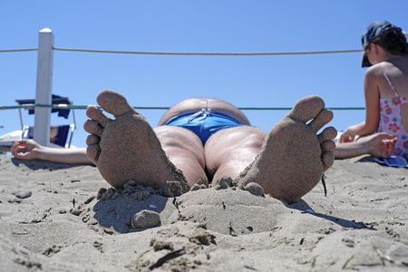 close up the foot of the sunbathing fat man photographed in a comical foreshortening