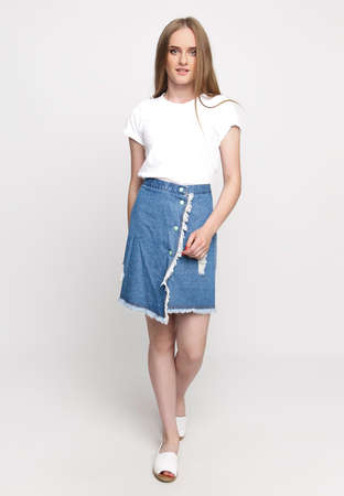 Photo for cute young slender woman in a white t-shirt and denim fashionable skirt on a white background. concept of advertising photo for once. - Royalty Free Image