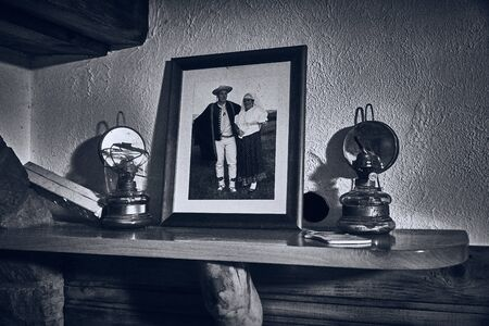 An old family photo of the housekeepers stands in a frame on the fireplace next to the kerosene lamp