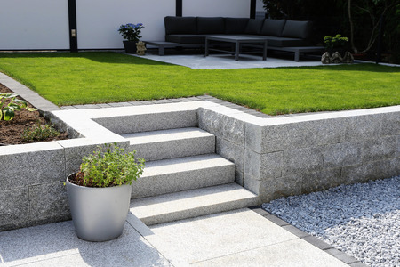 Photo pour Neat and tidy garden with granite wall and solid block steps - image libre de droit