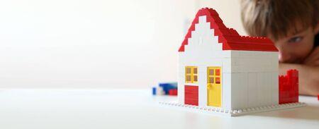Photo pour Boy builds a residential with building blocks - image libre de droit