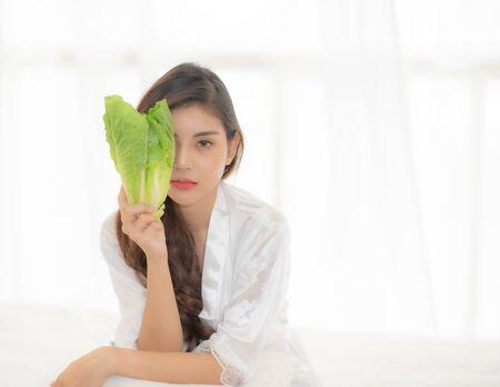 Photo pour Women wearing white clothes holding green vegetables. - image libre de droit