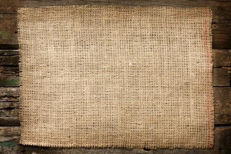 Burlap jute canvas vintage background on wooden boards