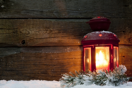 Christmas lantern light in night on snow and wooden boards