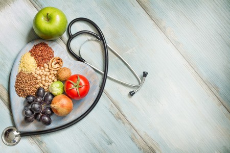 Foto de Healthy lifestyle and healthcare concept with food, heart and stethoscope - Imagen libre de derechos