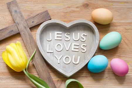 Foto de Easter cross and heart with inscription Jesus loves you on abstract wooden spring board - Imagen libre de derechos