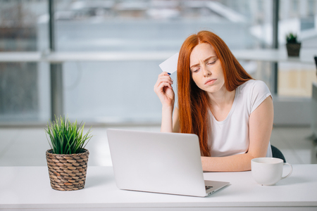 Photo for Thinking business woman sitting at table with laptop, holding empty credit card - Royalty Free Image