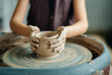Photo for Female potter working at throwing wheel at studio. Clay workshop - Royalty Free Image