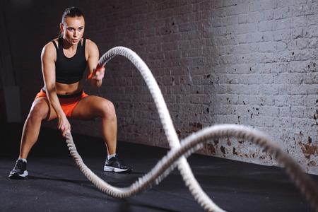 Foto de Athletic woman doing battle rope exercises at gym - Imagen libre de derechos
