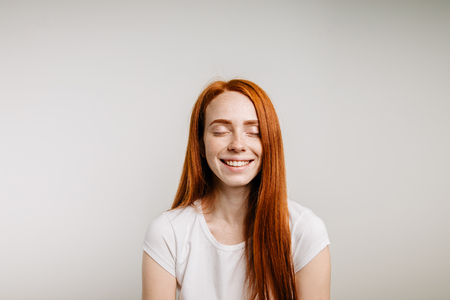 Photo pour Beautiful ginger girl smiling posing with closed eyes - image libre de droit