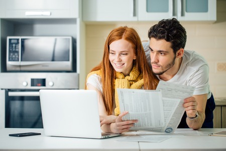 Photo pour cheerful young couple calculating their bills at home - image libre de droit