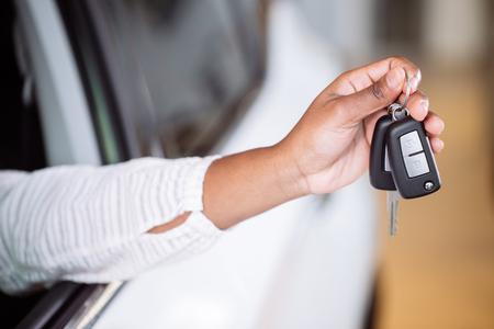 african woman with her new car showing key