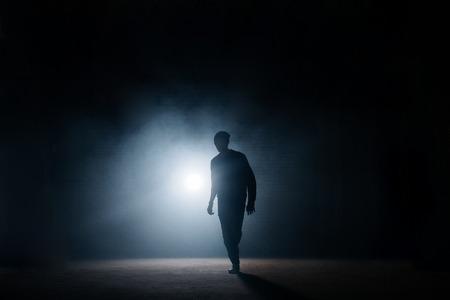 Photo pour dark silhouette of slim man walking on the street at night - image libre de droit