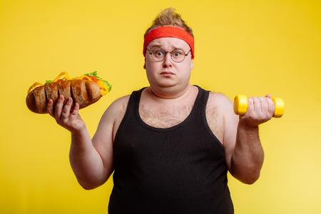 Photo pour Fat man choise between sport and fastfood - image libre de droit