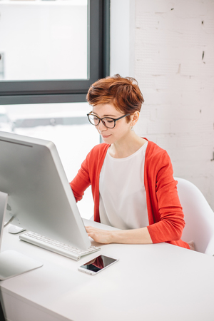 businesswoman typing on keyboard in bright office