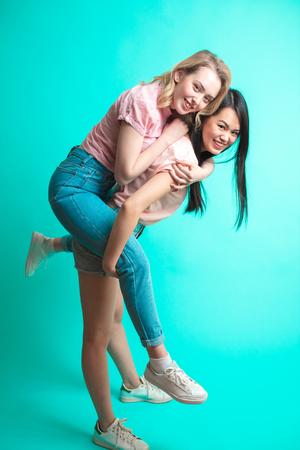 Two playful interacial girls piggybacking and having fun at studio