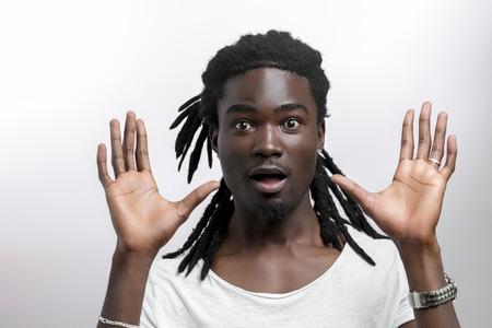 Foto de shocked African American man wearing white T-shirt looking at camera in surprise - Imagen libre de derechos