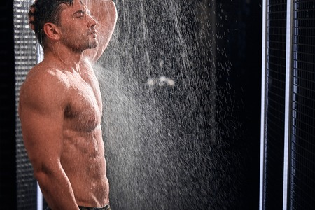 Foto de Handsome man taking shower, refreshing himself after a hot working day. - Imagen libre de derechos
