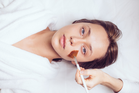 Photo pour gorgeous good looking girl lying on the bed and having a face mask - image libre de droit