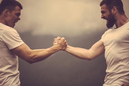 Photo pour Two caucasian athletes in sportive wear measuring forces at outdoor training - image libre de droit