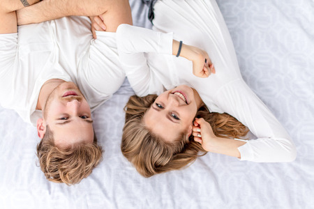 Photo pour positive smiling man and woman enjoying lying on the bed and posing to the camera - image libre de droit