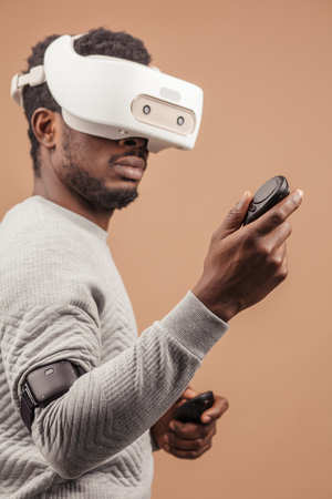 Black guy with virtual reality headset playing virtual Race game , moving hands with joysticks like a professional driver in street races , isolated on beige