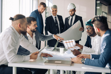 Multiracial group of constructors, builders, engineers and architects discussing blueprint at office. All men are dressed in business suits, and white shirts, one of them wears hardhat on head