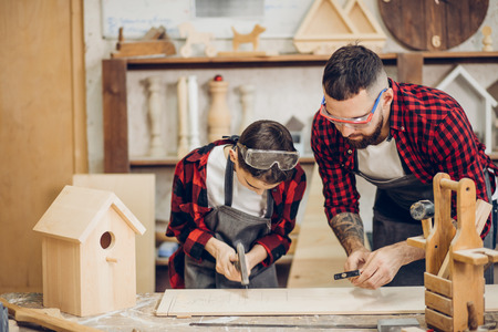 Young caucasian father and his pre-teen son working together in a wooden workshop, building a wooden bird house. Little boy dressed in apron and wearing protective glasses working with a hammer