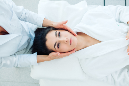 Beauty and cosmetology image of young woman face having face massage in spa salon, stimulating cell regeneration and the production of collagen with elastin, top view