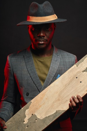 Portrait of energetic, sporty, self-assured handsome african man infashionable blazer suit holding longboard in hands, posing isolated in studio on dark background. Sport, Health anf Active lifestyle