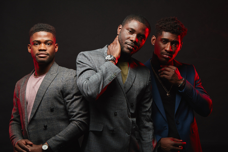 Photo pour Positive african ethnicity businessmen, well-dressed business partners wearing stylish suits looking at camera isolated in studio. Business Apparel, Fashion and Style, Mens Formal Clothing - image libre de droit